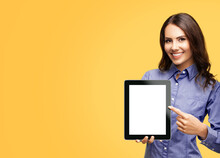 Happy Smiling Brunette Businesswoman Showing Blank Tablet Pc Monitor, With Copy Space Area For Some Text, Advertising Or Slogan, Isolated Over Orange Yellow Color Background. Business Woman At Studio.