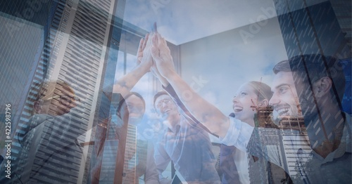 Business people high fiving each other at office against tall buildings