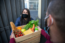Young Man Courier Delivers Online Shopping Basket With Fresh Fruit Vegetables To Woman Customer's Home During Coronavirus Covid-19 Pandemic Quarantine Wearing Protective Face Mask - Concept Delivery