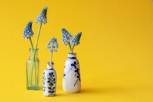 Two Small Vintage Vases With Blue Flowers, Antique Chinese Porcelain. With Blue Grape Flowers. Spring Scene Colorful Botanical Object. Yellow Background. Interior Design Decoration.