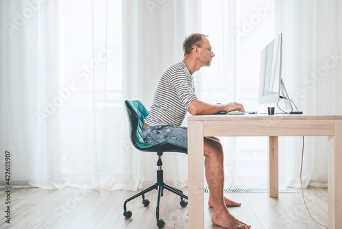 Fotografie, Obraz Barefoot Middle-aged writer man on a swivel chair typing down a text using the modern PC keyboard in the home living room