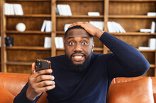Discouraged African-American Man Grabbed His Head, Holding A Smartphone, Looks At The Camera With Eyes Wide Opened, Portrait Of Shocked Black Guy With Phone In Hand