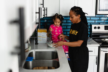 Black Army Mother Cooks Breakfast In Kitchen With Daughter