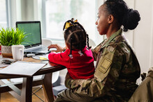 Focused Military Woman Working From Home At Laptop With Child