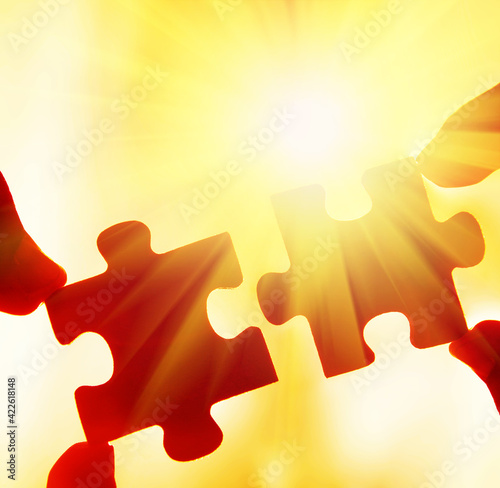 two hands trying to connect couple puzzle piece with sunset background. Jigsaw alone wooden puzzle against sun rays. one part of whole. symbol of association and connection. business strategy. Wall mural