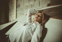 Young Blonde Female Lying On Wooden Planks Inside An Abandoned Building