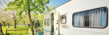 White Caravan Trailer On A Green Lawn In A Camping Site. Spring Landscape. Europe. Lifestyle, Travel, Tourism, Road Trip, Journey, Vacations, Recreation, Transportation, RV, Motorhome. Panoramic View