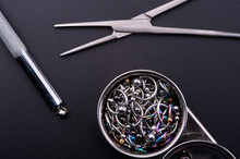 Piercing Earrings, Stainless Steel Clips For Disinfection On A Black Background