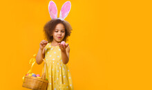 A Surprized Black Girl With Rabbit Ears On Her Head With A Basket Of Colored Eggs In Her Hands.
