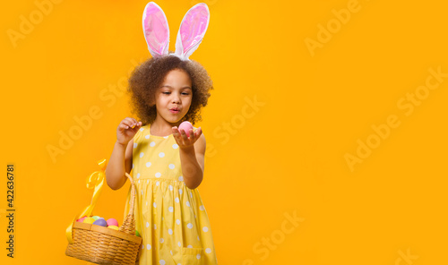 Vászonkép A surprized Black girl with rabbit ears on her head with a basket of colored eggs in her hands