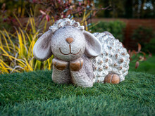 Caen, France, March 2021. Figurine Easter Lamb On Green Grass In The Garden, Symbol Of Easter.