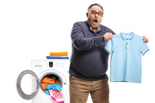 Surprised Mature Man Holding A Shrunken T-shirt In Front Of A Washing Macine