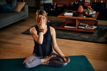 A Middle-aged Woman Sitting In A Lotus Yoga Pose And Meditating With Eyes Closed.