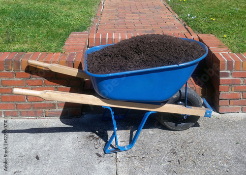Photo Spring wheelbarrow filled with mulch.