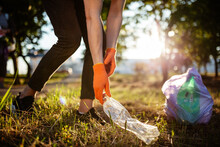 Man Picks Up Litter Outdoors, Collecting Used Plastic Bottle Trash. A Volunteer Cleans Up The Park On A Sunny Bright Day. Clearing, Pollution, Ecology And Plastic Concept.