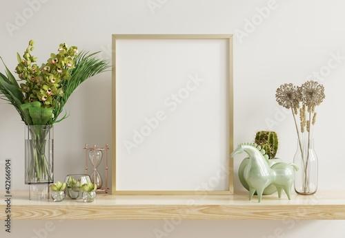 Fototapeta White mock up frame with vertical gold metal frame on the shelf. obraz