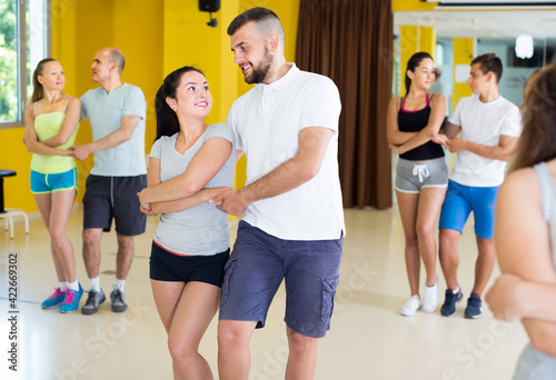 Obraz na plátne Enthusiastic dancing couples learning salsa at dance class