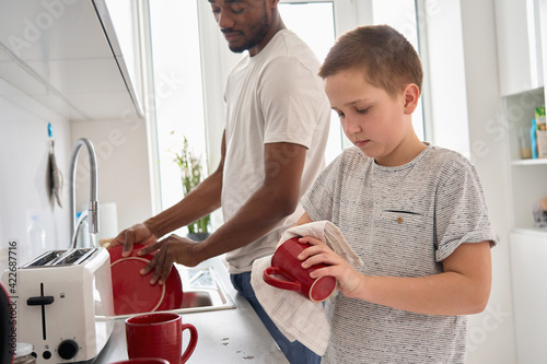 Papel de parede Teenage Caucasian boy son helping young African American Black father washing and wiping dishes together after mixed race diverse family dinner doing housework chores standing in kitchen at home