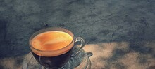 Cup Of Coffee On Cement Table. Orange Tone.