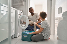 Diverse Teen Son And African Dad Doing Laundry Together At Home. Black Father And White Teenage Boy Putting Dirty Clothes In Washing Machine Doing Family Housework Household Chores In Bathroom.