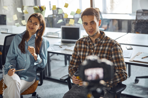 Two young office workers being filmed with the camera