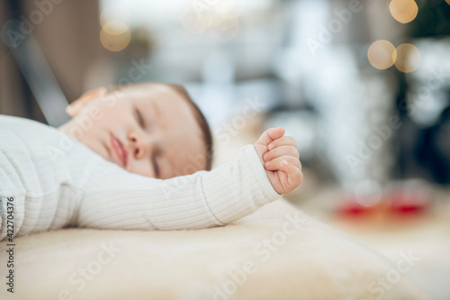 Fingers clenched into fist on hand of sleeping baby