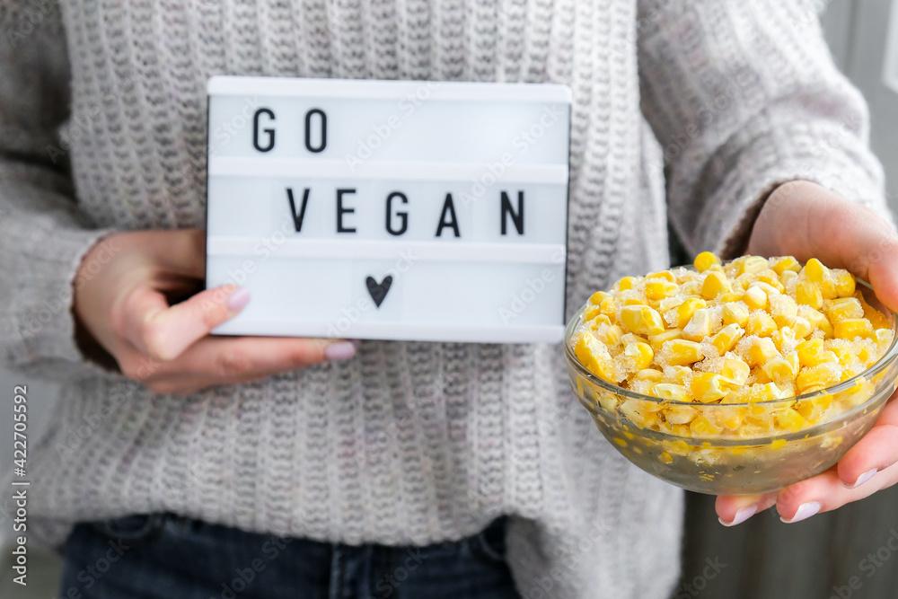 Obraz Lightbox with text GO VEGAN in female hands. Veganism, vegetarian healthy lifestyle. Frozen food in bowl. Yellow corn fototapeta, plakat