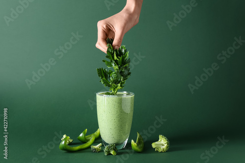 Female hand with glass of tasty smoothie on color background