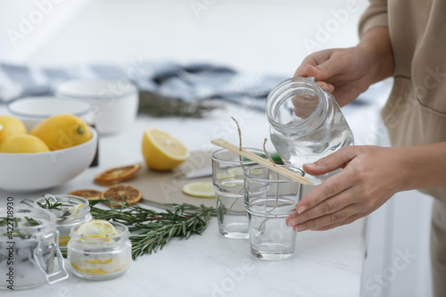 Woman making natural mosquito repellent candles at white table, closeup