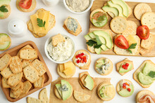 Different Snacks With Salted Crackers On White Wooden Table, Flat Lay