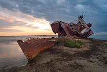 An Old Abandoned Ship On The Shore Of The Drying Up Aral Sea. Kazakhstan. Abandoned Ships Sawn For Scrap By Local Residents. Ecological Disaster Of The Aral Sea