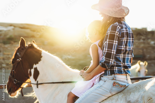Fototapeta Happy family mother and daughter having fun riding horse inside ranch