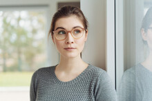 Attractive Young Woman Wearing Eyeglasses Looking Aside Through A Window