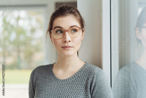 Obraz Attractive young woman wearing eyeglasses looking aside through a window - fototapety do salonu