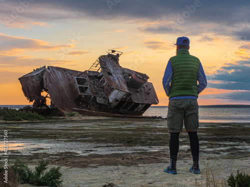 Fotografija A man stands on the shores of the Aral Sea by an old abandoned ship