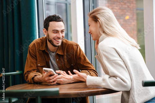 Fototapeta Happy young couple talking while sitting in cafe indoors obraz