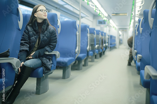 Fototapeta girl sits on a train / winter transport, one adult girl sits by the train window traveling obraz