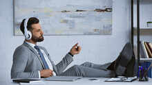 Young Manager Listening Music In Headphones While Sitting With Legs On Desk In Office