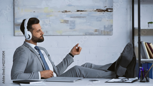 Obraz young manager listening music in headphones while sitting with legs on desk in office - fototapety do salonu