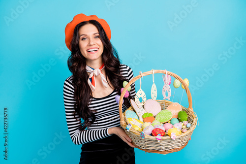 Portrait of charming cheerful lady hands hold demonstrate easter basket isolated on blue color background
