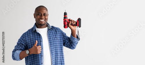 Positive african american man holding electric drill and showing thumb up, isolated on white background