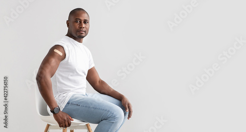 Obraz Positive black man with plaster on shoulder after injection of covid-19 vaccine, panorama with free space - fototapety do salonu