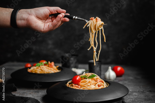 Fototapeta Pasta with feta cheese and baked tomatoes in a black plate. Spaghetti obraz