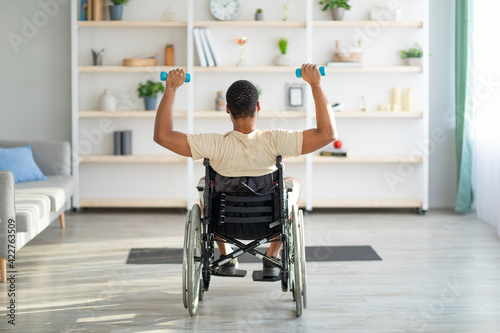 Canvas Print Back view of impaired black guy in wheelchair exercising with dumbbells at home