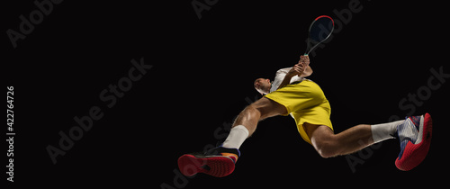 Fototapeta Young caucasian tennis player in action, motion isolated on black background, look from the bottom. Concept of sport, movement, energy and dynamic. obraz
