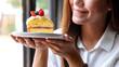Leinwandbild Motiv Closeup image of a beautiful young asian woman holding a piece of cake in a plate