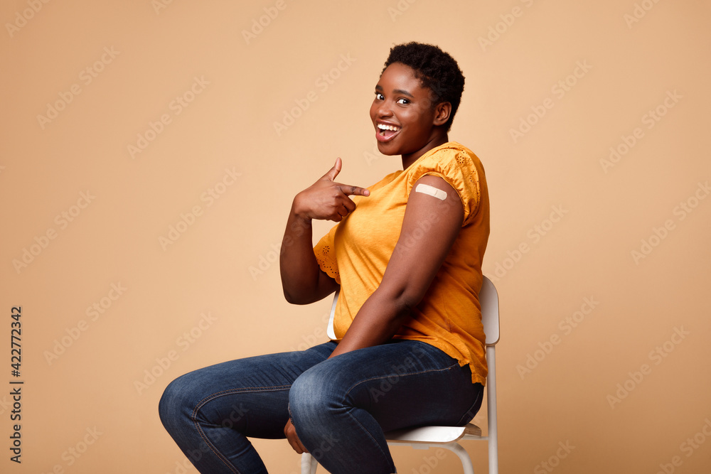 Fototapeta Black Lady Showing Arm After Getting Vaccine Injection, Beige Background