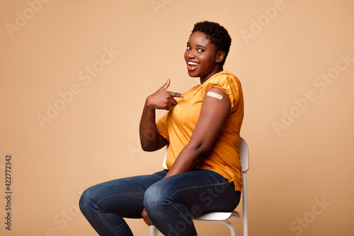 Obraz Black Lady Showing Arm After Getting Vaccine Injection, Beige Background - fototapety do salonu