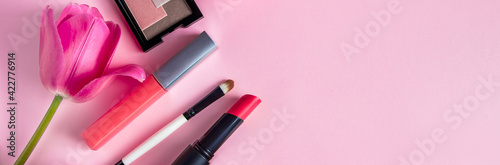 Set of cosmetics and flowers on a pink background. Makeup and beauty products.