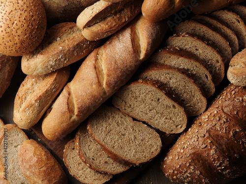 Fototapeta Assortment of baked bread on wooden table background obraz